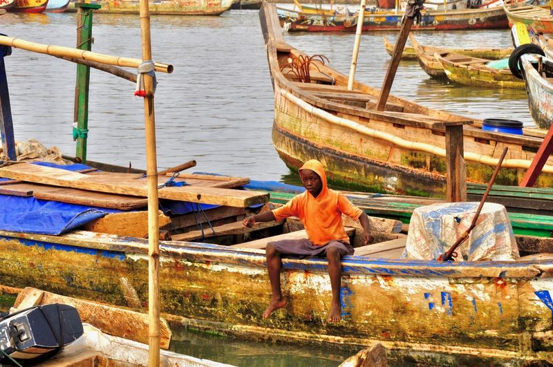A boy is sitting on a traditional african fishing boat