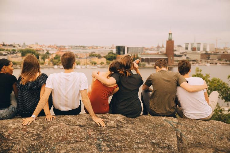 Rear view of people sitting on walkway in city against sky