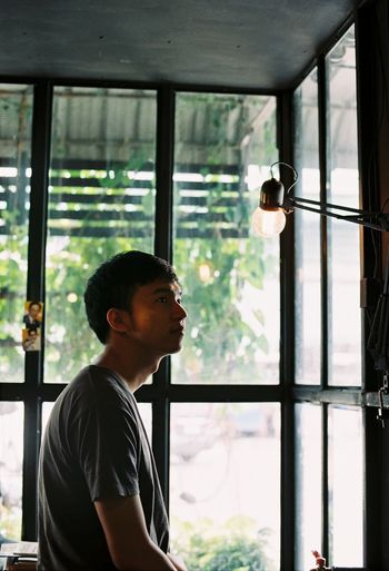 Side view of young man looking at illuminated light bulb by window