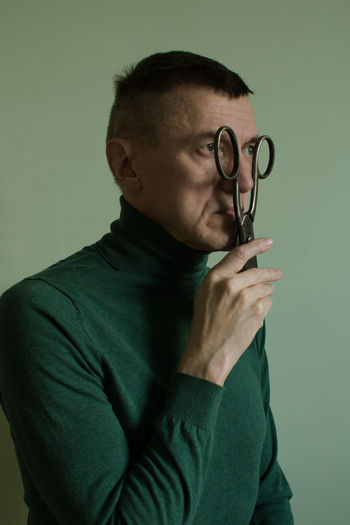 Mature man holding scissors looking away against wall