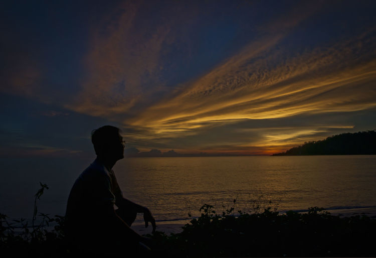 silhouette scene Beach Beauty In Nature Cloud - Sky Idyllic Leisure Activity Lifestyles Looking At View Nature One Person Orange Color Outdoors Real People Scenics - Nature Sea Side View Silhouette Sky Sunset Tranquil Scene Tranquility Water