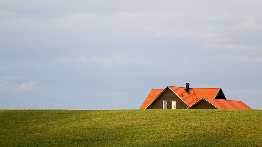House On Grassy Field Against Cloudy Sky
