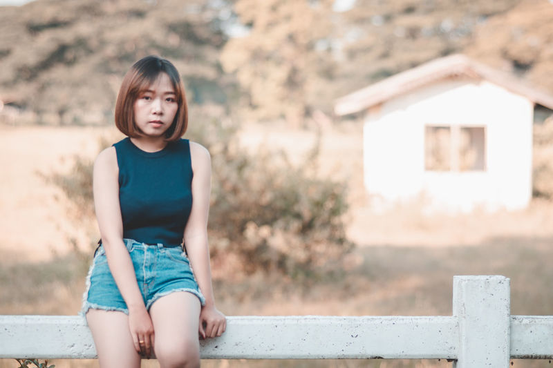 Asian Woman Asian Girl Asian Teen Beautiful Woman Casual Clothing Day Females Focus On Foreground Front View Girls Hairstyle Innocence Leisure Activity Lifestyles Looking At Camera One Person Outdoors Portrait Real People Shorts Sitting Women