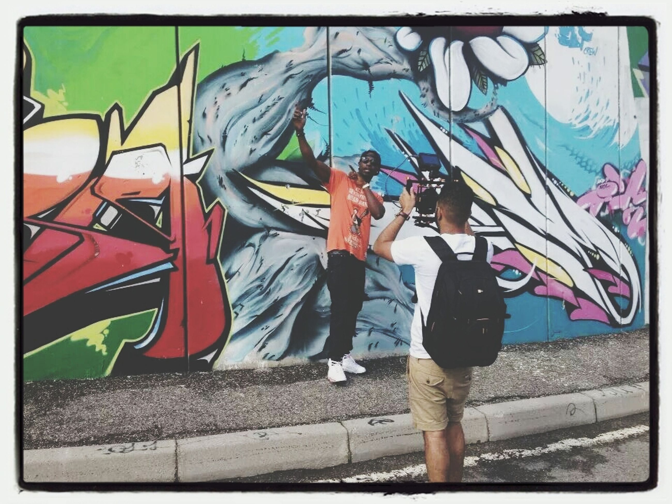 transfer print, auto post production filter, lifestyles, graffiti, leisure activity, full length, casual clothing, standing, men, transportation, day, wall - building feature, street, outdoors, built structure, person, art, creativity