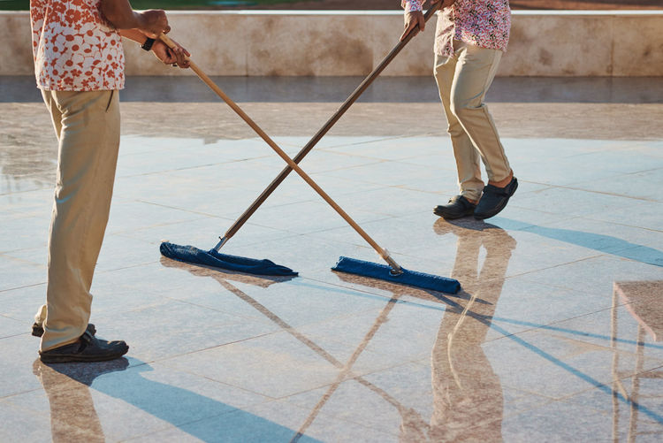 Low section of people cleaning tiled floor