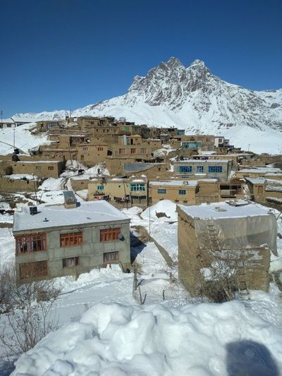 Houses on snow covered mountain against sky