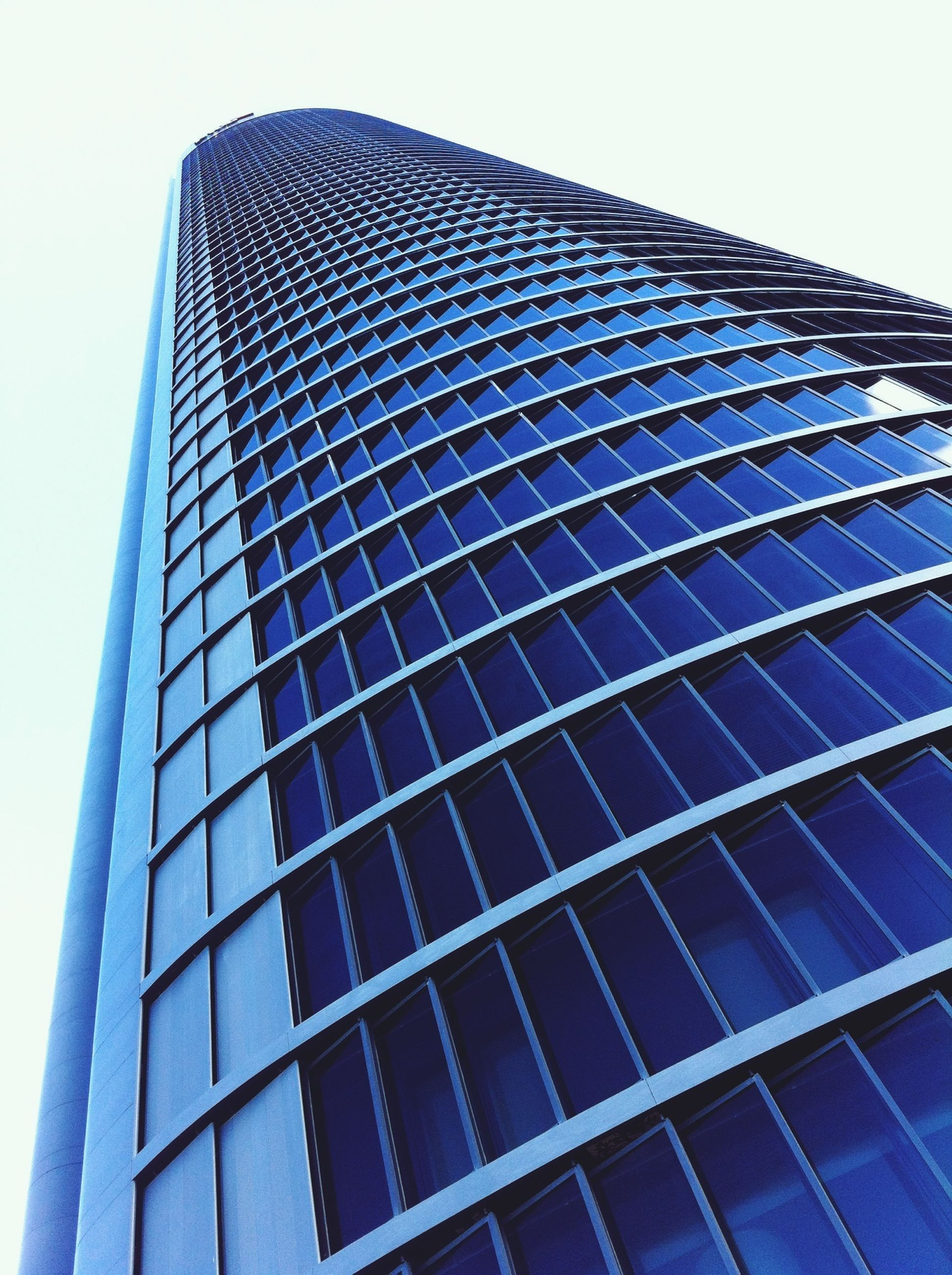 low angle view, architecture, building exterior, built structure, modern, office building, skyscraper, tall - high, city, tower, glass - material, building, clear sky, reflection, sky, tall, day, outdoors, no people, blue