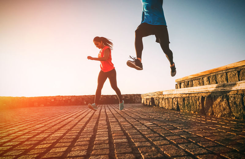 Couple running on promenade against clear sky during sunset