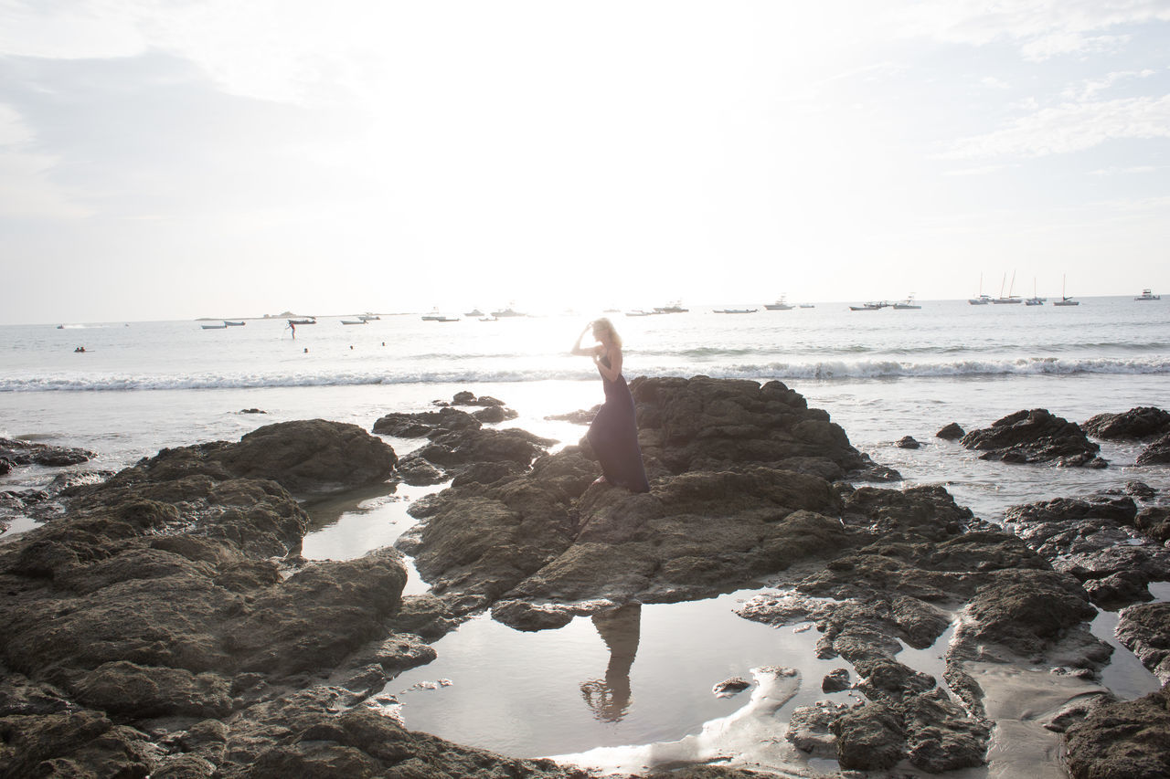 sea, water, horizon over water, real people, one person, beach, leisure activity, rock - object, shore, standing, nature, day, beauty in nature, sky, lifestyles, outdoors, tranquility, scenics, women, full length, wave, young adult, people