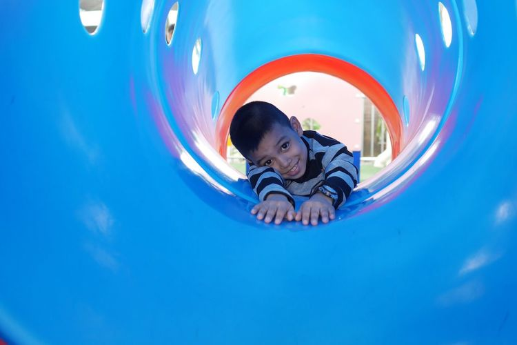 Portrait of smiling boy lying in slide at playground