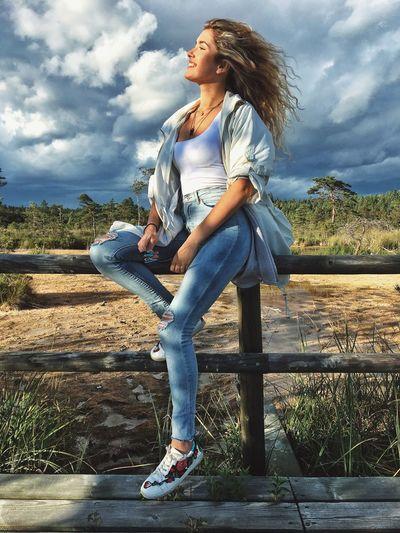 Full length of woman looking away against sky