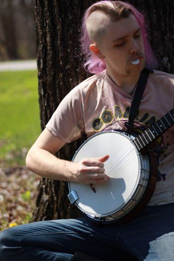 Music Casual Clothing Young Adult Playing Outdoors Musical Instrument Close-up Sun Shade Sitting Outside Banjo Player Tree Banjo Real People Music Musician Mustache Carbondale Midday Relaxing Jeans Sitting Southern Illinois  Purple Purple Hair