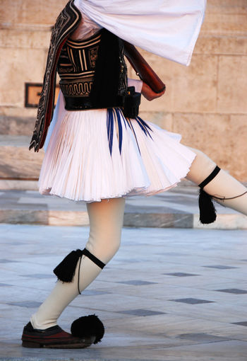 Evzone soldier with a traditional uniform and holding a gun parading at syntagma square in Athens, Greece Evzones Parading Soldier Adult Athens Clothing Dancing Day Dress Fashion Focus On Foreground Full Length Greece High Heels Human Leg Leisure Activity Lifestyles Motion One Person Real People Shoe Skill  Skirt Women