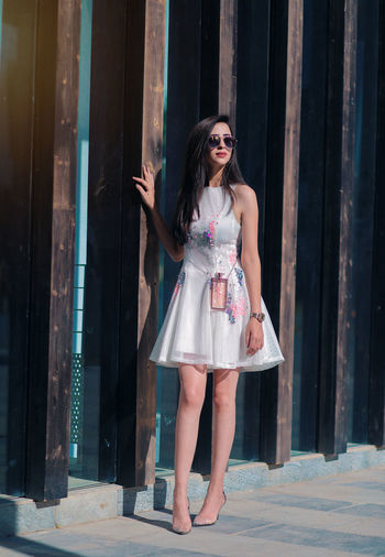 Full length of woman wearing sunglasses standing by wall