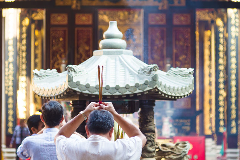 Rear View Of Man Holding Incenses At Chinese Temple