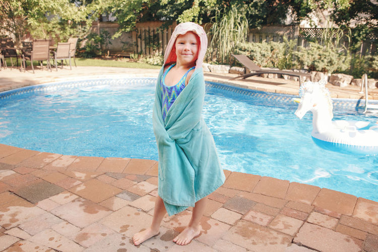 Girl wrapped in beach towel standing by pool. summer outdoor water activity for kids.
