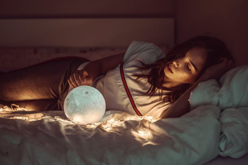 Woman Sleeping With Sphere And Fairy Lights On Bed At Home