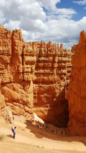 Hikers visiting navajo loop at bryce canyon national park against sky