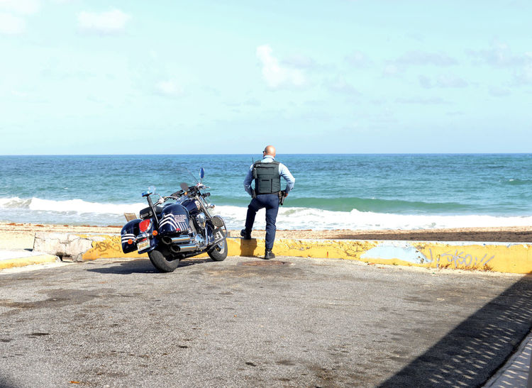 Beach Casual Clothing Cycling Day Full Length Horizon Over Water Land Vehicle Men Mode Of Transport Motorcycle Ocean Outdoors Police Policeman Rear View Sea Shore Sky Solitude Tranquil Scene Tranquility Transportation Water