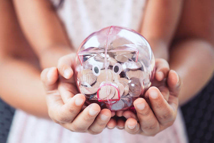 Midsection of mother and daughter holding piggy bank
