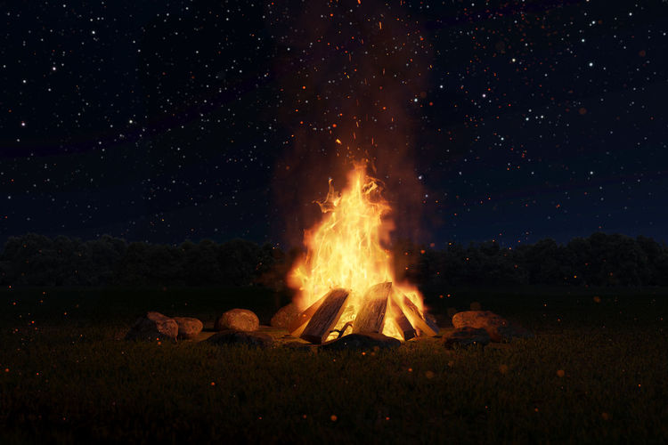 Bonfire on field against sky at night