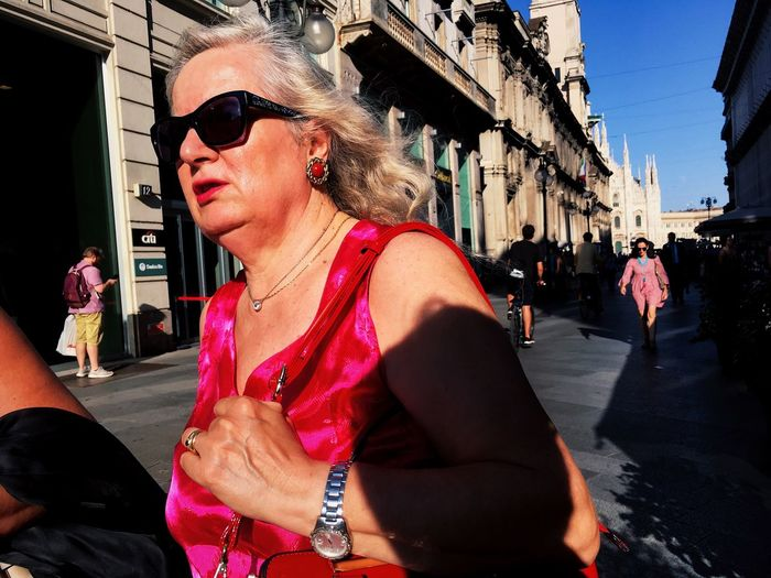 Young woman wearing sunglasses in city against sky