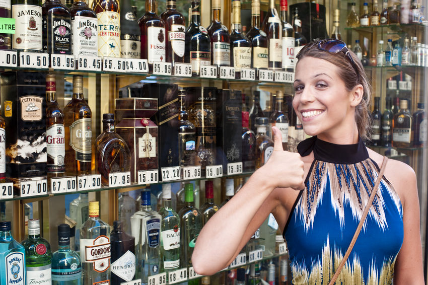 Young attractive tourist woman in the mediterranean Adult Adults Only Alcohol Blond Hair Bottle Cheerful Choice Consumerism Front View Happiness Indoors  Large Group Of Objects Looking At Camera One Person One Woman Only Only Women People Perfume Perfume Counter Portrait Retail  Shelf Smiling Store Variation