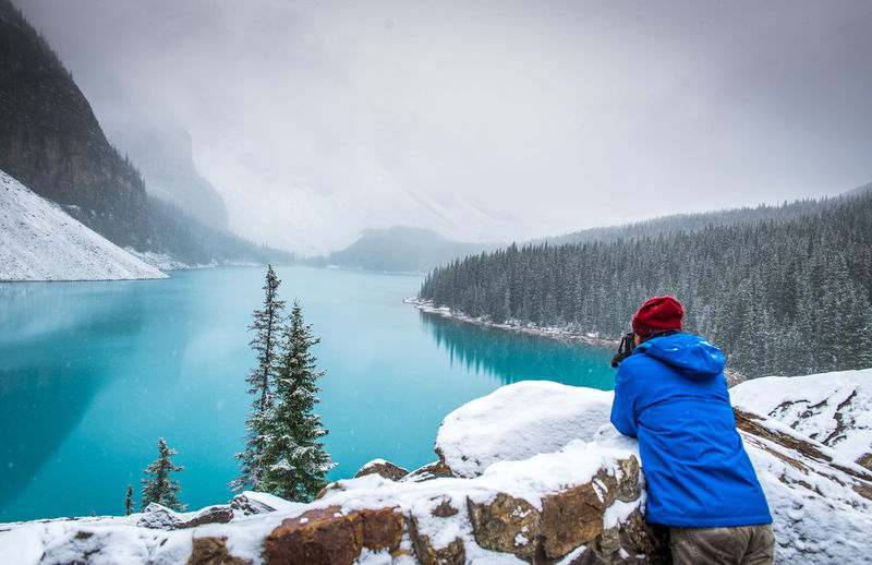 Rear View Of Man Standing By Snow On Retaining Wall Against Frozen Lake