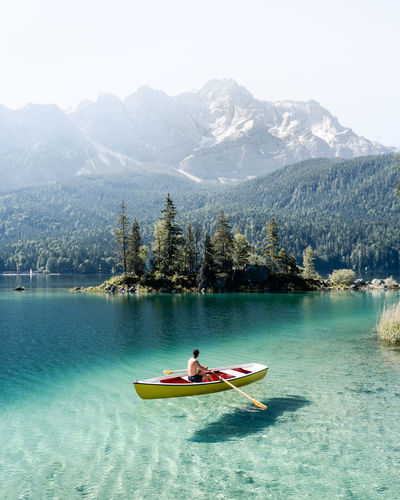 Man on boat sailing in lake by mountain