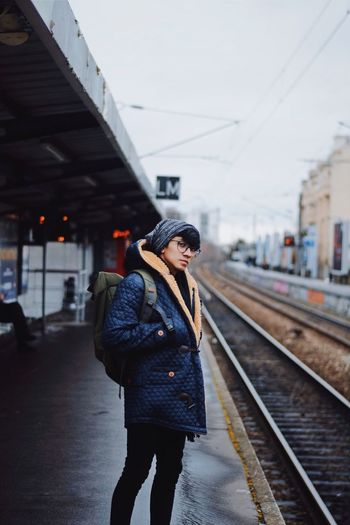 Portrait of young man standing on railroad station platform
