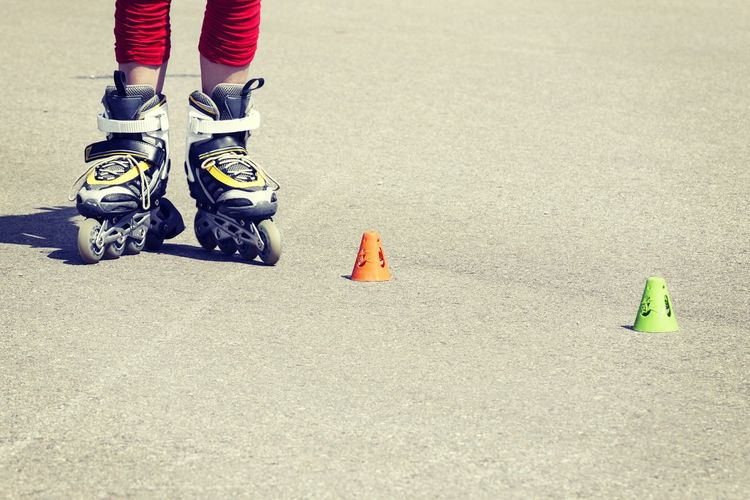 Low section of girl wearing skates while standing during sunny day
