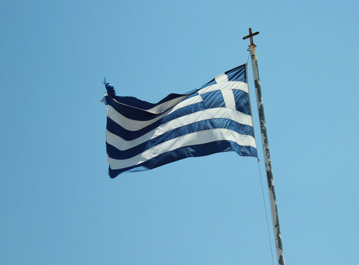 Low angle view of greece flag against clear blue sky