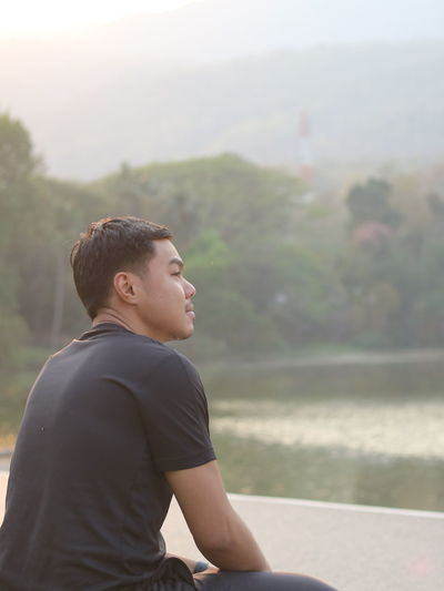 Side view of young man looking at lake