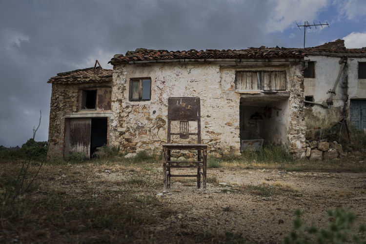 Old abandoned house in a abandoned village with a lonely chair in front of it in a cloudy day