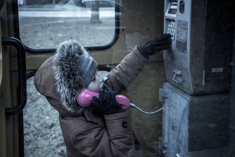 Oldschool calling Boy Callbox Child Day One Person Outdoors People Standing Telephone Booth Warm Clothing Young The City Light Millennial Pink