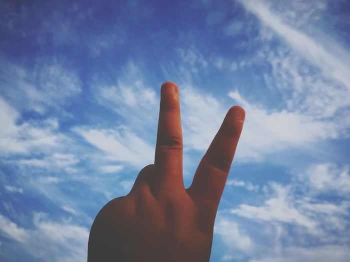 Low angle view of man gesturing peace sign against sky
