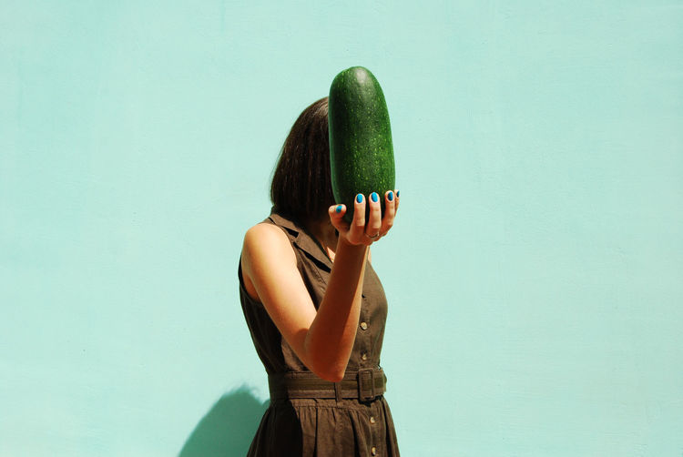Woman Holding Large Cucumber Over Green Background