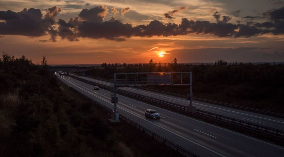 High angle view of cars on highway against sky during sunset
