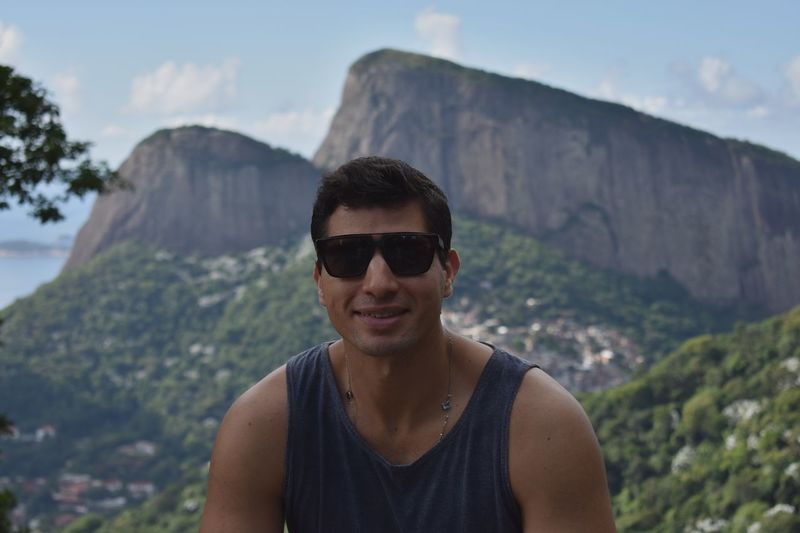 Portrait of smiling man wearing sunglasses against mountains