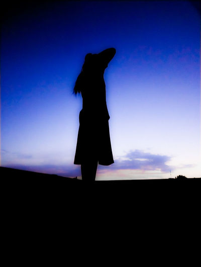 Silhouette woman standing on field at sunset