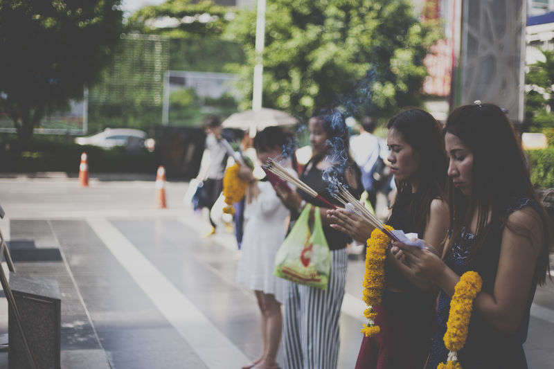 a group of women pray to a Buddhist image Buddhism Buddhist Casual Clothing City Street Day Enjoyment Focus On Foreground Fun Group Of People Meditation Merit Person Pray Prayer Praying Street Thailand
