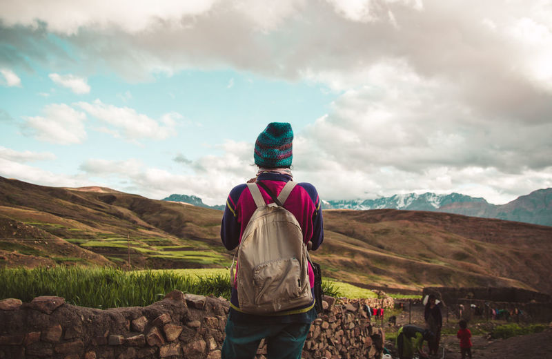 Rear view of woman standing on landscape against mountain