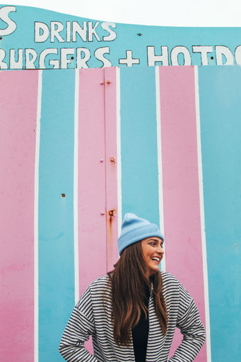 Portrait of smiling woman standing against pink wall