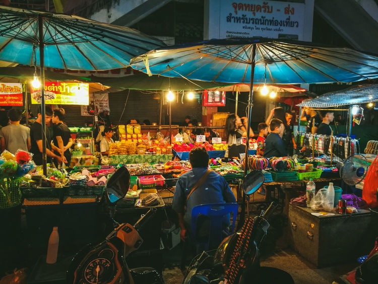 Overnight Success Illuminated Sitting Person Men Market Retail  Market Stall Side View Selling Night Market Vendor Outdoor Restaurant Small Business Restaurant Patio Umbrella Outdoors Social Gathering Group Of Objects Choice
