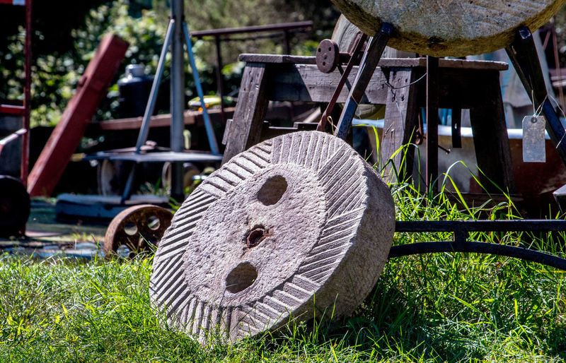 very large very heavy grinding stone from the past, used for grinding grains Antique Heavy Junk Yard Tools Of The Trade Abandoned Architecture Close-up Day Equipment Field Focus On Foreground Grass Grinding Wheel Growth Land Machinery Metal Nature No People Old Outdoors Plant Stone Wheel Tool Wheel