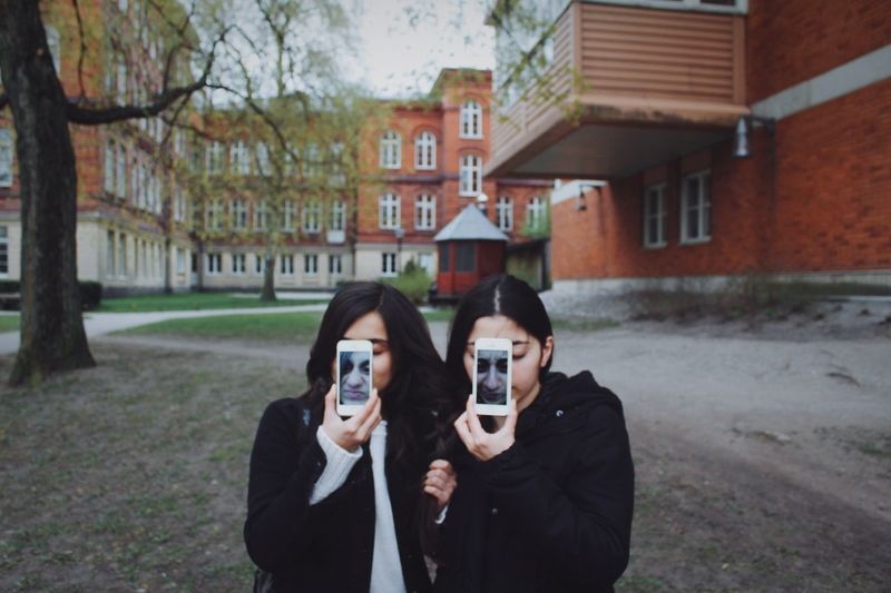 Female Friends Taking Selfie With Smart Phone While Standing Against Buildings
