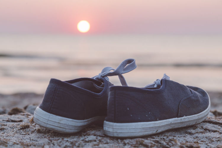Close-up of shoes on beach