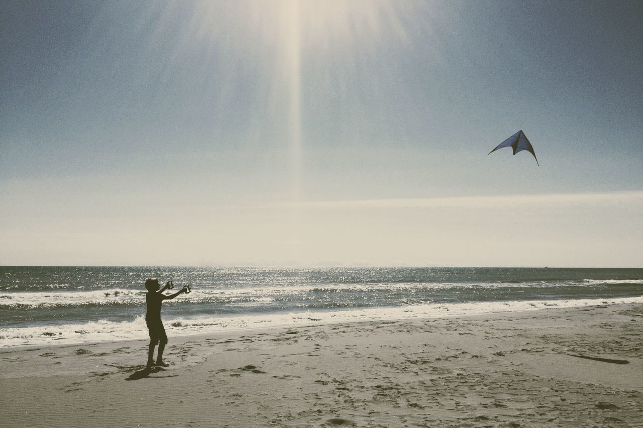 Boy Flying Kite At Beach Against Sky