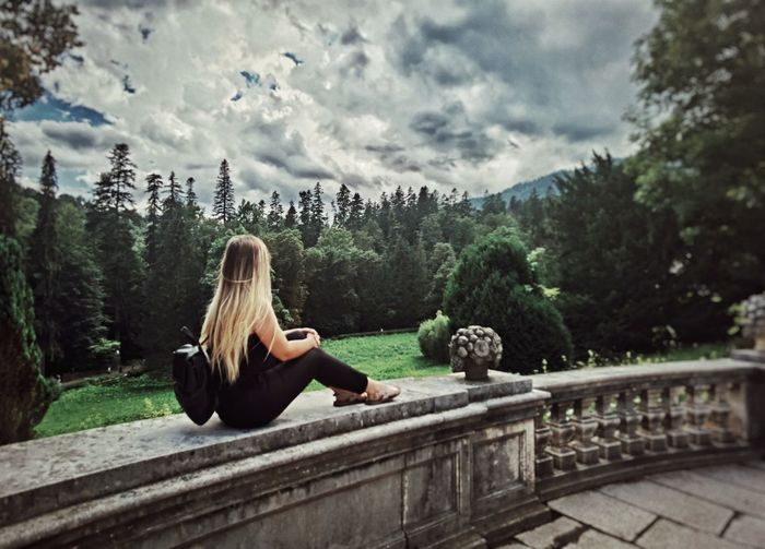 Full length of woman sitting on retaining wall against sky