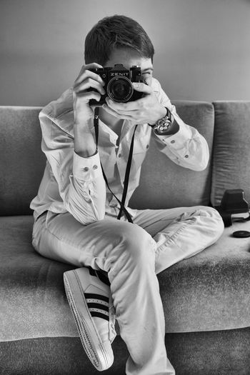 man with analog camera Boys Camera Casual Clothing Childhood Day Elementary Age Full Length Home Interior Indoors  Leisure Activity Lifestyles Living Room Minimalism One Person People Photography Themes Portrait Real People Sitting Sofa Technology Watch Young Adult